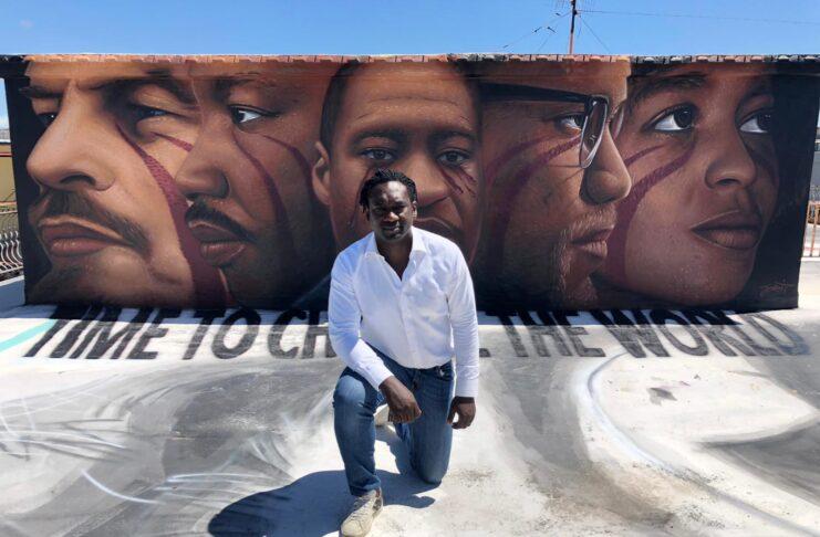 Hilarry Sedu in front of the Jorit mural